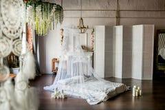 sitio del Desván-estilo con una cama, un toldo, una chimenea blanca con un centro de flores, una pantalla blanca, un espejo grand imágenes de archivo libres de regalías