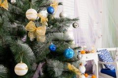 Sitio del interior del ` s del Año Nuevo El árbol de navidad adornado con los globos coloridos y los regalos mienten en el piso B Imagen de archivo