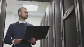 Sitio del servidor del control del ingeniero de las TIC del datacenter que sostiene el ordenador portátil almacen de metraje de vídeo