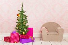 Sitio del vintage con el árbol de navidad, los regalos y la silla Imagenes de archivo