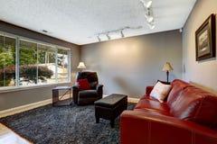 Sitio en color gris con el sofá rojo brillante Imágenes de archivo libres de regalías