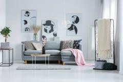 Sitio en colores pastel con el sofá gris Fotos de archivo libres de regalías