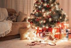 Sitio en oscuridad con el árbol de navidad, la decoración y los regalos iluminados, interior del hogar en la noche Imagenes de archivo