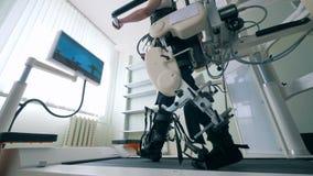 Sitio médico con un paciente masculino que experimenta un entrenamiento de la pista que camina Dispositivo médico moderno de la r almacen de metraje de vídeo