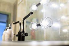 Sitio moderno con todas las instalaciones, mirada muy cómoda, luces, espejo del baño Una botella de jabón líquido cerca del lavab Fotos de archivo libres de regalías