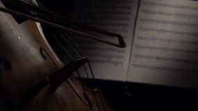 Sitio oscuro con el arco del violoncelo en secuencias Cierre para arriba Vista lateral metrajes