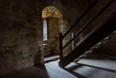 Sitio oscuro con la ventana de las paredes de piedra y la escalera de madera Fotos de archivo libres de regalías