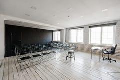 Sitio para la conferencia con muchas sillas oscuras Las paredes son blancas, interior del desván A la derecha hay una puerta en imagen de archivo libre de regalías