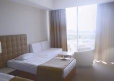 Sitio soleado en el hotel en colores claros con dos camas imágenes de archivo libres de regalías