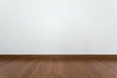 Sitio vacío con el piso marrón de la lamina de madera y la pared blanca del mortero Fotos de archivo