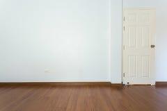 Sitio vacío con el piso marrón de la lamina de madera y la pared blanca del mortero fotos de archivo libres de regalías