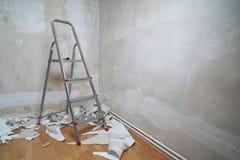 Sitio vacío con la escalera de las paredes desnudas y pedazos viejos del papel pintado en piso durante la renovación con el espac imagenes de archivo