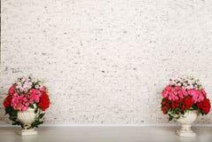Sitio vacío con la pared de ladrillo blanca y las flores hermosas Fotos de archivo libres de regalías