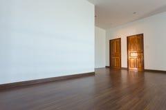 Sitio vacío, fondo blanco de la pared del mortero y piso laminado de madera fotos de archivo libres de regalías