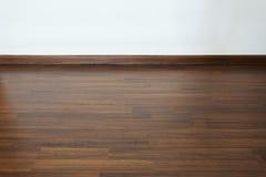 Sitio vacío, fondo blanco de la pared del mortero y piso laminado de madera fotos de archivo