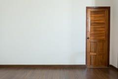 Sitio vacío, fondo blanco de la pared del mortero y piso laminado de madera foto de archivo