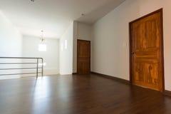 Sitio vacío, fondo blanco de la pared del mortero y piso laminado de madera imágenes de archivo libres de regalías