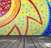 Sitio vacío con la pared colorida de la teja de mosaico y el fondo de madera del interior del piso Foto de archivo