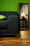 Sitio verde del salón con el sofá y la lámpara en espejo Foto de archivo libre de regalías