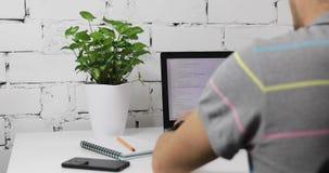 Sitio web programado del programador en el ordenador portátil en oficina almacen de metraje de vídeo