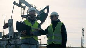Sito dell'estrazione di combustibile con un esperto maschio che dà istruzioni a altro Energia, olio, gas, impianto di perforazion stock footage