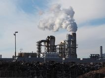 Sito industriale con i fumaioli di fumo dietro i materiali crudi del metallo fotografie stock