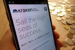 Sito Web di scambio di cryptocurrency di Kraken visualizzato sullo smartphone e sulla pila di monete fotografia stock