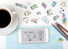 Sito Web e concetto mobile di sviluppo di app Tazza di caffè e del telefono cellulare su una scrivania bianca Fotografia Stock