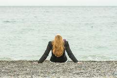 She sits back on a pebble beach by sea on a cloudy day, his head thrown back Royalty Free Stock Image