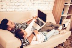 Sitt på soffan handbärbar dator Fader och dotter i lägenhet Spendera tid tillsammans dagfader s Man som spelar med flickan vitt arkivbild