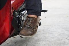 Sitt p? din motorcykel och starta motorn med fotstartst?ngen eller sparkstartknappen fotografering för bildbyråer