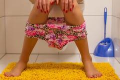 Sitt på toalett Arkivfoto