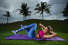Sitt ups - att öva för konditionman sitter upp utanför i gräs i summ Arkivfoton
