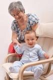 Sitta barnvakt på stol och skratta med farmodern royaltyfria bilder