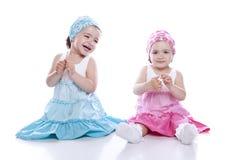 sitta för flickor som är tvilling- Arkivfoton