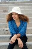 Sitta för hatt för ung kvinna som bärande vitt är ensamt utomhus Royaltyfri Foto