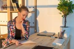 Sitta för kvinna som är fundersamt, koncentrerat och att skriva, läsa som arbetar på den ljusa studion Stående för sidosikt av en royaltyfria bilder