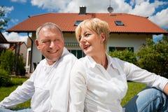 sitta för pensionär för par som främre home är deras royaltyfria foton