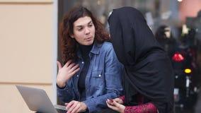 Sitta för två kvinnligt vänner som är utvändigt, och använda bärbara datorn Argt kulturellt kamratskap Den unga muslimkvinnan i s stock video
