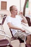 Sitta för ung man som är utomhus- i ett kafé i sommar Royaltyfri Bild