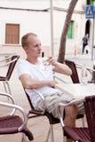 Sitta för ung man som är utomhus- i ett kafé i sommar Royaltyfri Fotografi