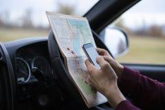 Sitta i händerna för bilchaufför som rymmer översikten och sökande av utfarten som förloras i skog f royaltyfria bilder