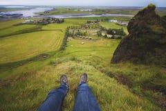Sitta på berget framme av den Kirkjubaejarklaustur byn arkivbilder
