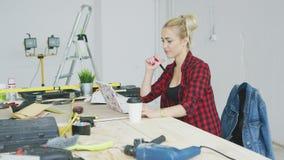 Sitta på den kvinnliga användande bärbara datorn för arbetsbänk stock video