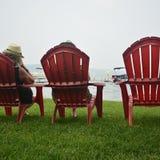 Sitta på en Adirondack stol på gräset vid stranden på en mellanvästern- sjö Royaltyfri Foto