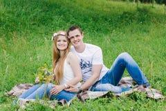 Sitta på en pläd på ett gräs som lyckligt ler arkivfoton