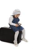 Sitta på en resväskaflicka som spelar med telefonen arkivbilder