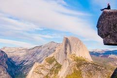 Sitta på kanten av glaciärpunkt i den Yosemite nationalparken Royaltyfri Foto