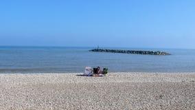 Sitta på stranden på Sidmouth royaltyfri bild
