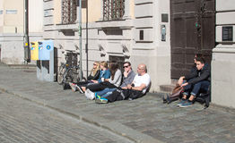 Sitta på trottoaren och koppla av i solen Arkivbilder